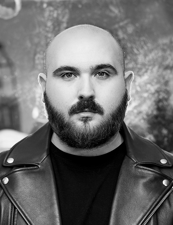 A black and white headshot of the artist, Nicholas Aiden